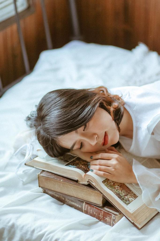 Vrouw slaapt op stapel boeken
