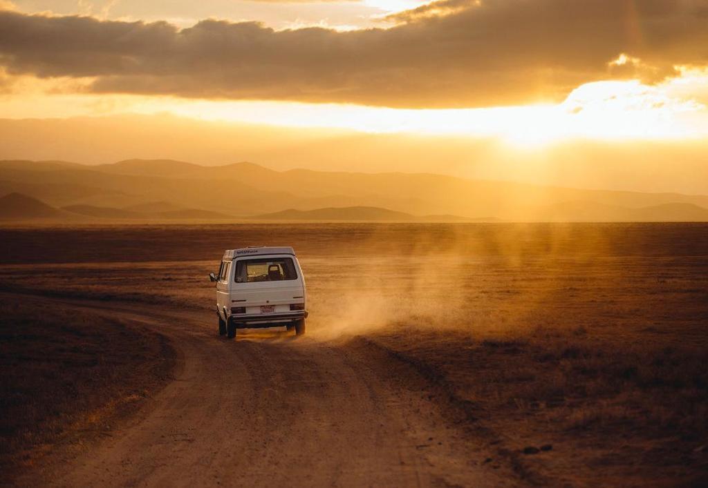 Wit busje rijdt op stoffige weg met wijde horizon